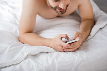 cropped view of young man lying in bed and chatting on smartphone