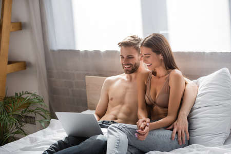 cheerful lovers smiling while using laptop in bedroom