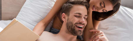 laughing man touching sensual girlfriend holding book in bedroom, banner