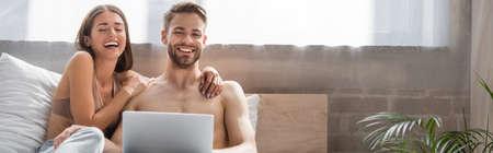 laughing woman touching shirtless boyfriend using laptop in bed, banner