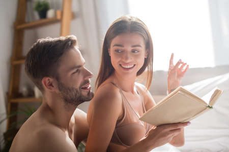 smiling woman holding book and pointing with finger near shirtless boyfriend