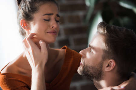 tender man touching face of crying girlfriend while calming her at home