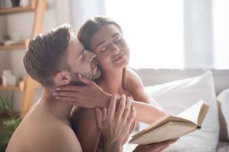 sexy woman holding book while shirtless boyfriend touching and kissing her in bedroom