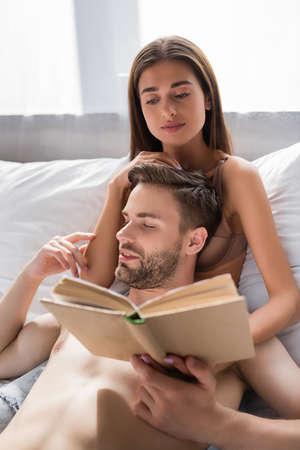 shirtless man touching sexy girlfriend reading book in bedroom Zdjęcie Seryjne