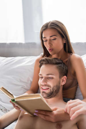 sexy young couple reading book in bed together