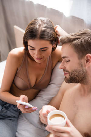 young woman in bra showing smartphone to shirtless boyfriend on blurred foreground
