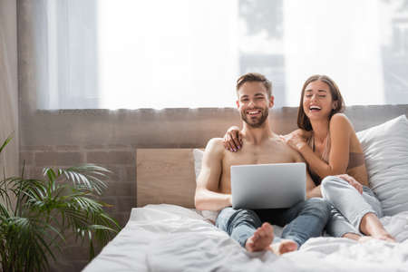laughing man and woman using laptop together in bedroom