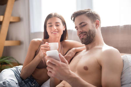 shirtless man chatting on smartphone near smiling girlfriend holding cup of coffee on blurred background Zdjęcie Seryjne