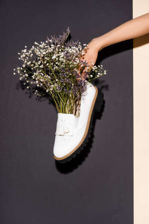 cropped view of woman holding white shoe with wildflowers on black background 免版税图像