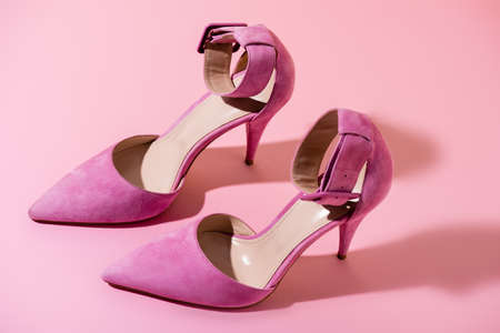 pair of elegant suede heeled shoes on pink background