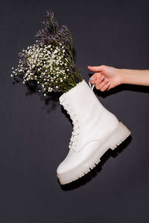 cropped view of woman holding white boot with wildflowers on black background