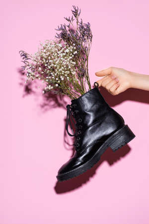 cropped view of woman holding black boot with wildflowers on pink background