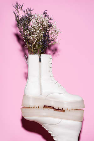 white boots with wildflowers on pink background