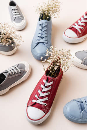casual sneakers and wildflowers on white background 免版税图像