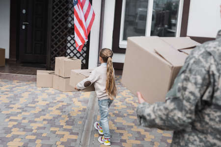 Back view of girl carrying cardboard box near house with blurred father on foreground