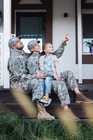 Happy military mother and father pointing with finger, looking away, sitting with daughter on house threshold on blurred foreground