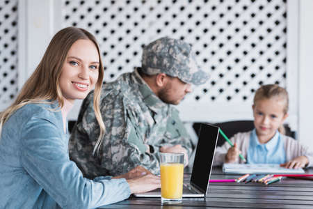 Smiling wife looking at camera, typing on laptop, while sitting at table with blurred military man and girl on background