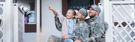 Happy military mother and father sitting near daughter pointing with finger, on backyard, banner