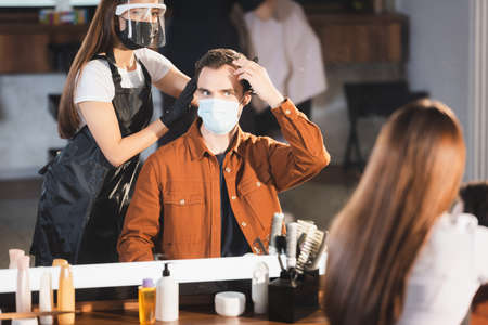 mirror reflection of hairdresser touching hair of client, blurred foreground 免版税图像 - 157952986
