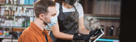 hairdresser in protective equipment showing digital tablet to man in medical mask, banner