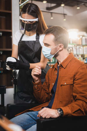barber in face shield holding container with hair balsam near client in medical mask