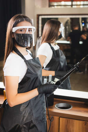 young barber in face shield, apron and latex gloves holding curling iron on blurred background 免版税图像 - 157952994