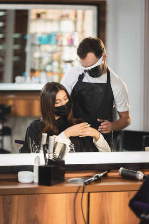 mirror reflection of hairdresser in face shield near woman in medical mask with hairdressing tools on blurred foreground 免版税图像 - 157952999