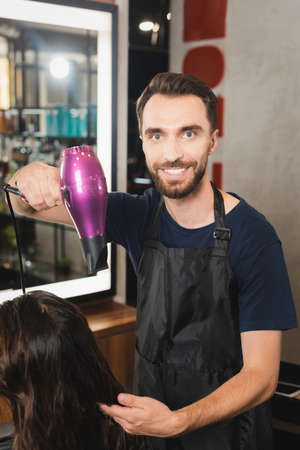 cheerful hairdresser drying hair of woman while looking at camera