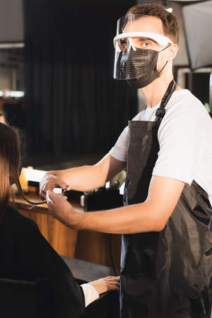 barber in face shield cutting hair of client while looking at camera