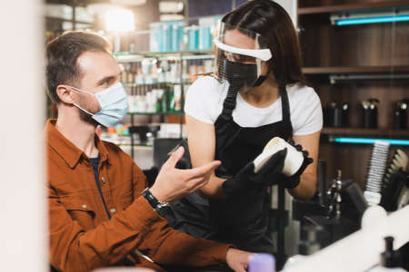 man in medical mask pointing with hand near hairdresser in protective equipment holding container with hair balsam, blurred foreground