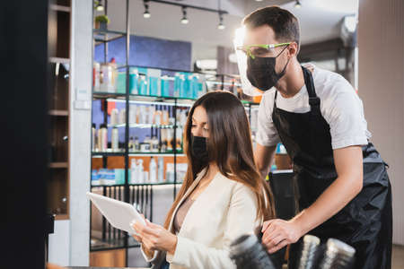 barber in face shield near woman in medical mask holding digital tablet, blurred background