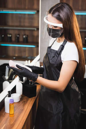 hairstylist in face shield, apron and latex gloves holding bottle of shampoo 免版税图像