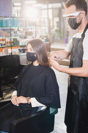 hairstylist in apron and face shield cutting hair of woman in medical mask