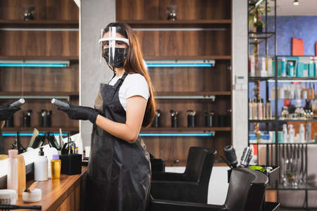 hairstylist in face shield and latex gloves holding comb and looking at camera