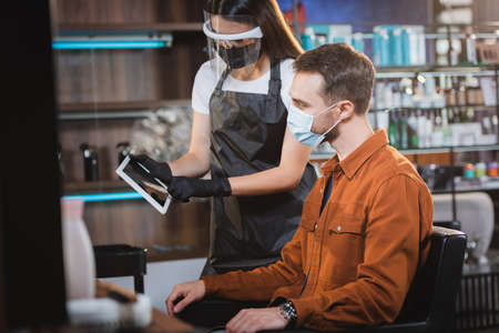 barber in face shield and latex gloves holding digital tablet near man in medical mask, blurred foreground 免版税图像