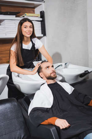 smiling hairdresser looking at camera while washing hair of young man 免版税图像 - 157952858