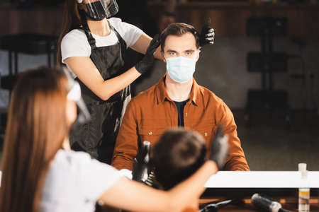 mirror reflection of hairdresser in face shield and latex gloves touching hair of client on blurred foreground 免版税图像 - 157952860