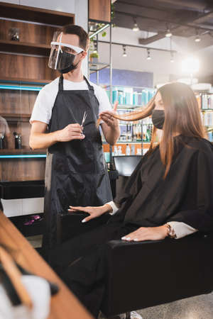 hairdresser in face shield holding scissors and touching hair of client, blurred foreground