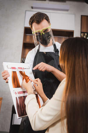 hairdresser in face shield pointing with finger at hair colors palette near woman touching sample on blurred foreground 免版税图像
