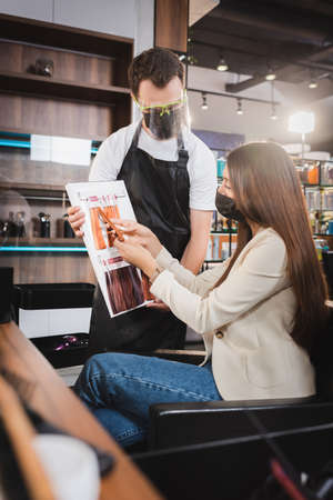 hairdresser in protective equipment holding hair colors palette near woman touching sample, blurred foreground 免版税图像 - 157952868