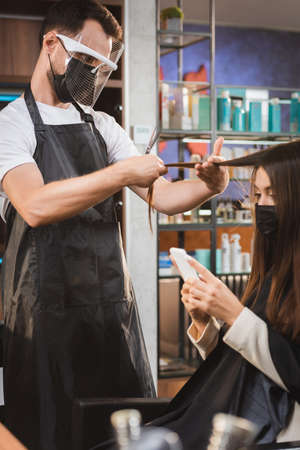hairdresser in protective equipment cutting hair of woman using smartphone, blurred background 免版税图像