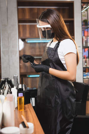 hairdresser in apron, face shield and latex gloves holding scissors near cosmetics on blurred foreground 免版税图像