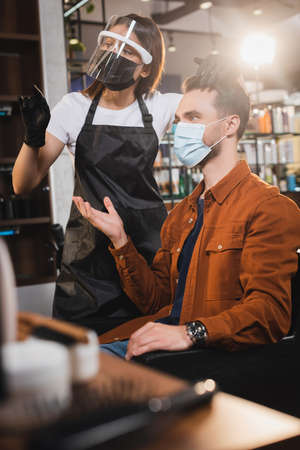 hairstylist in face shield and latex gloves pointing with finger, and client in medical mask pointing with hand, blurred foreground