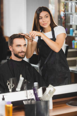 mirror reflection of barber cutting hair of bearded man with blurred hairdressing tools on foreground