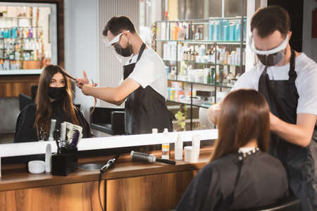 mirror reflection of hairdresser cutting hair of client in medical mask, blurred foreground