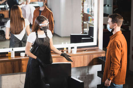 hairdresser in protective equipment pointing with hands at armchair near client in medical mask 免版税图像