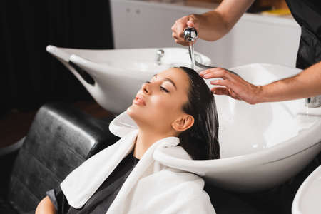 hairstylist washing hair of young woman in barbershop