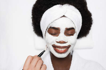 Top view of smiling african american woman with face mask near spa therapist with cosmetic brush in spa salon