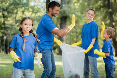 girl looking at camera while parents holding recycled bag and giving high five on blurred background, ecology concept