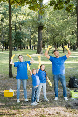 excited family showing success gesture near rubbish containers with plastic waste, ecology concept Stock fotó